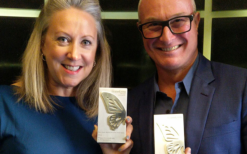Two people holding silver Transform Awards