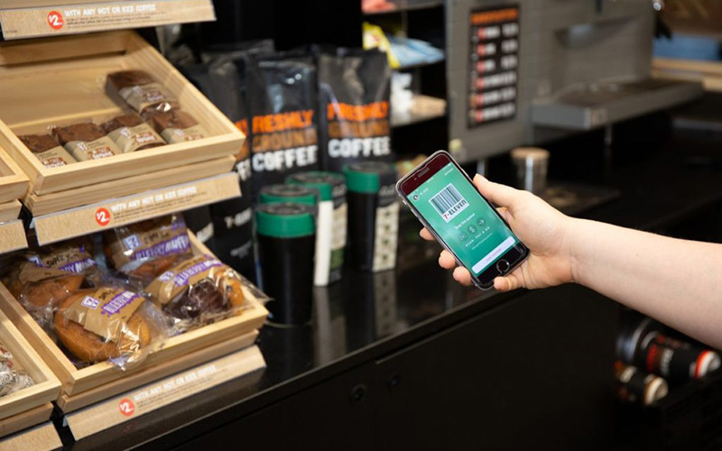 Hand holding phone showing 7 Eleven app in a store